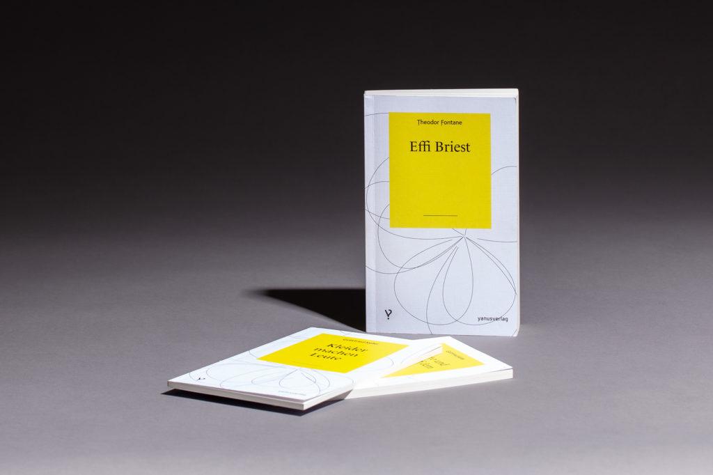 Yanus Verlag Bücher stehend und liegend auf grauem Hintergrund