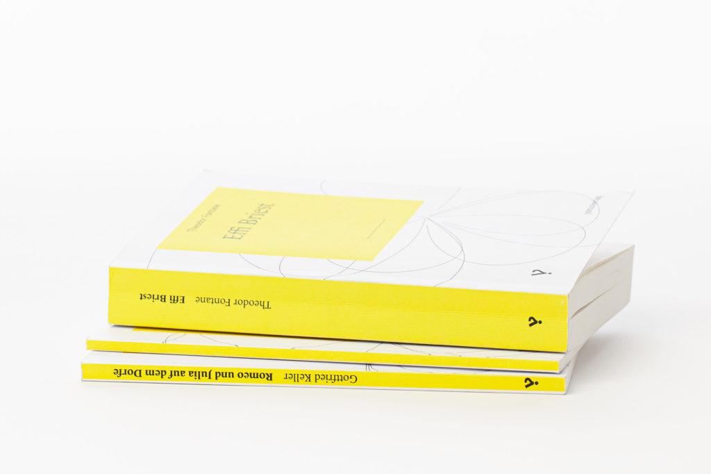 gelbe Buchrücken des Yanus Verlag. Gestaltet von HAGEN Julian Grafik Design