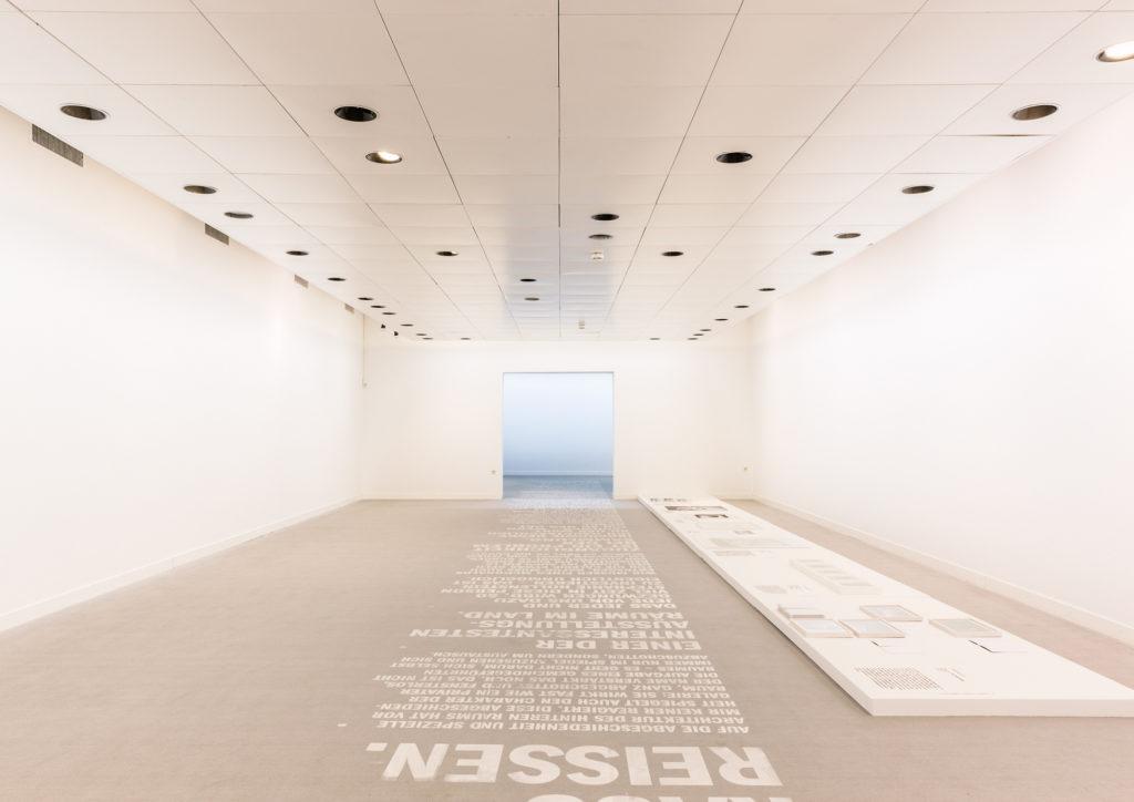 Der Grafiker und Gestalter Julian Hagen wurde daraufhin eingeladen, für Auszüge und Zitate aus diesen Gesprächen ein Display zu erarbeiten, das diese Geschichten im Raum sichtbar werden lässt. Ausgangspunkt war für ihn der dominante Teppichboden in der Galerie, den er als Layout auffasst, um mittels Siebdruckverfahren die dem Raum eingeschriebenen Erzählungen auch tatsächlich in aufwendiger Handarbeit einzuschreiben