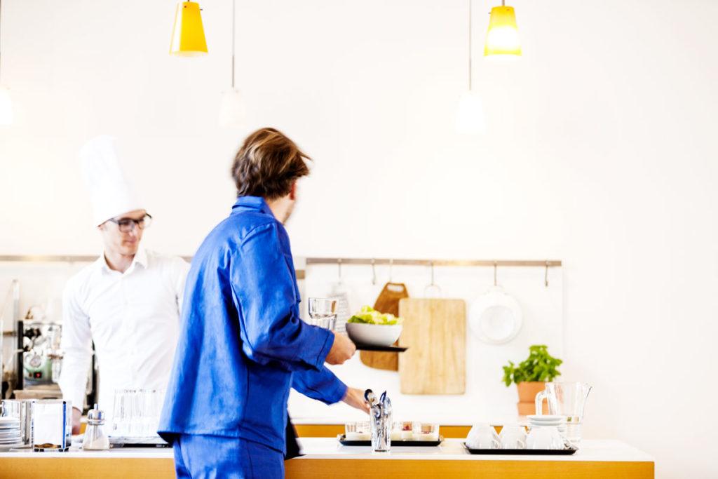 typische Situation einer Kantinen Mittagspause. Bauarbeiter in Blaumann Kleidung bekommt Essen serviert