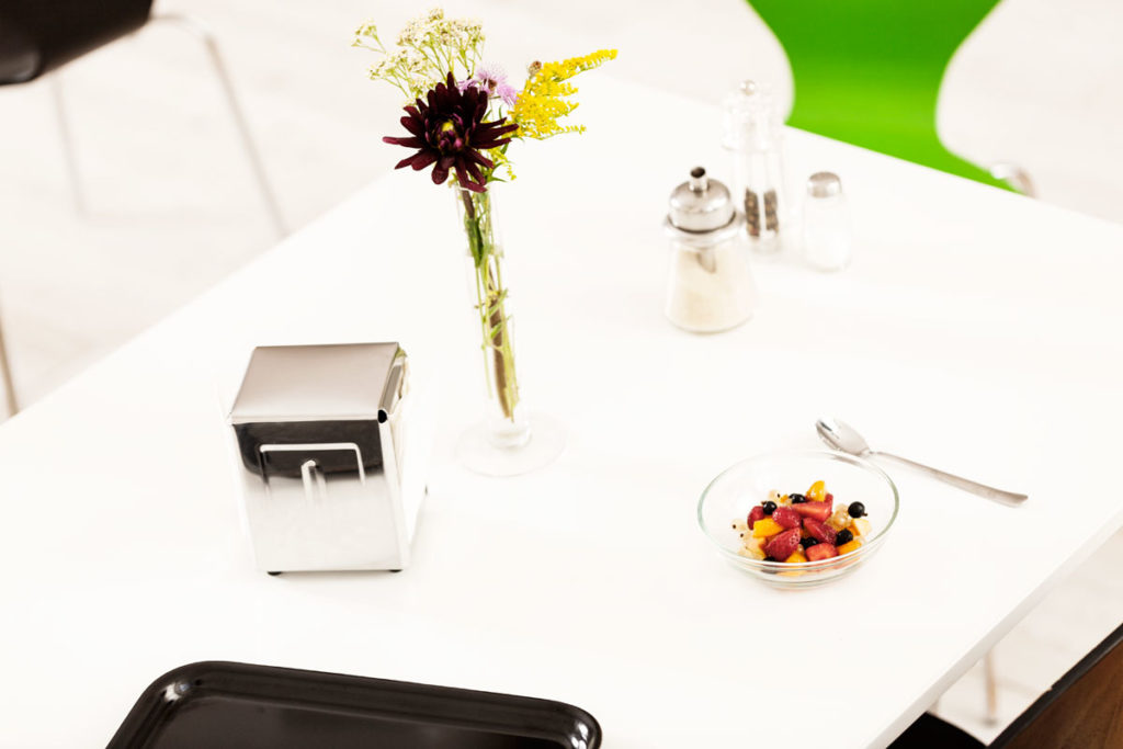 typische Situation einer Kantinen Mittagspause mit Tischgesprächen und Blumen auf dem Tisch